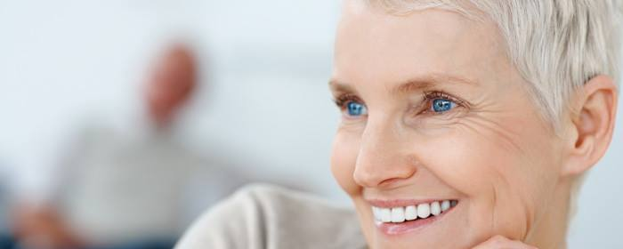 An image of a mature woman smiling, having received a new denture from from Love-Teeth Dental Practice.