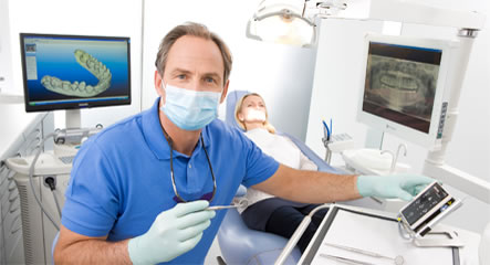 An image of a male dental surgeon, holding a small dental mirror and carrying our dental work on a patient in the dentists chair.