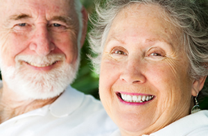 An image of two elderly people, one male and one female, smiling after treatment with Love-Teeth Dental Practice.