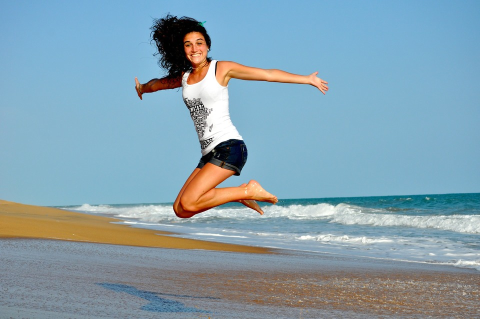 An image of a woman jumping in the air, smiling and showing her healthy teeth.